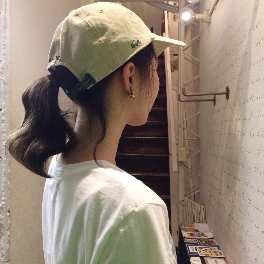 キャップをかぶる髪を結わいた女性